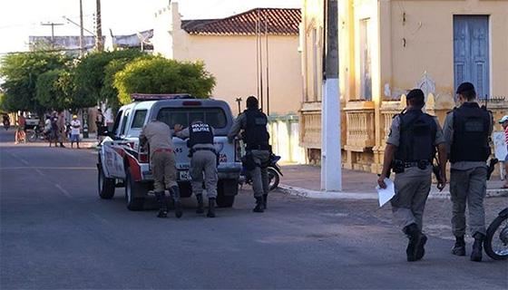 Policiais empurrando viatura